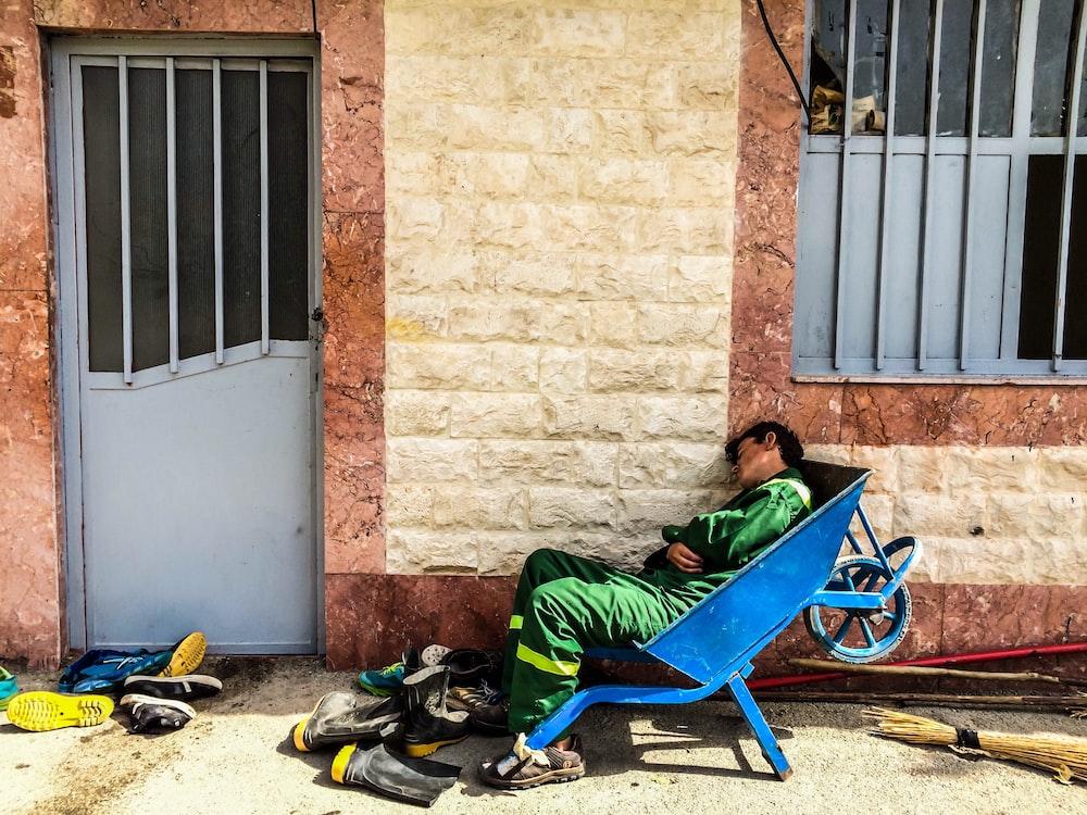person sleeping on wheelbarrow