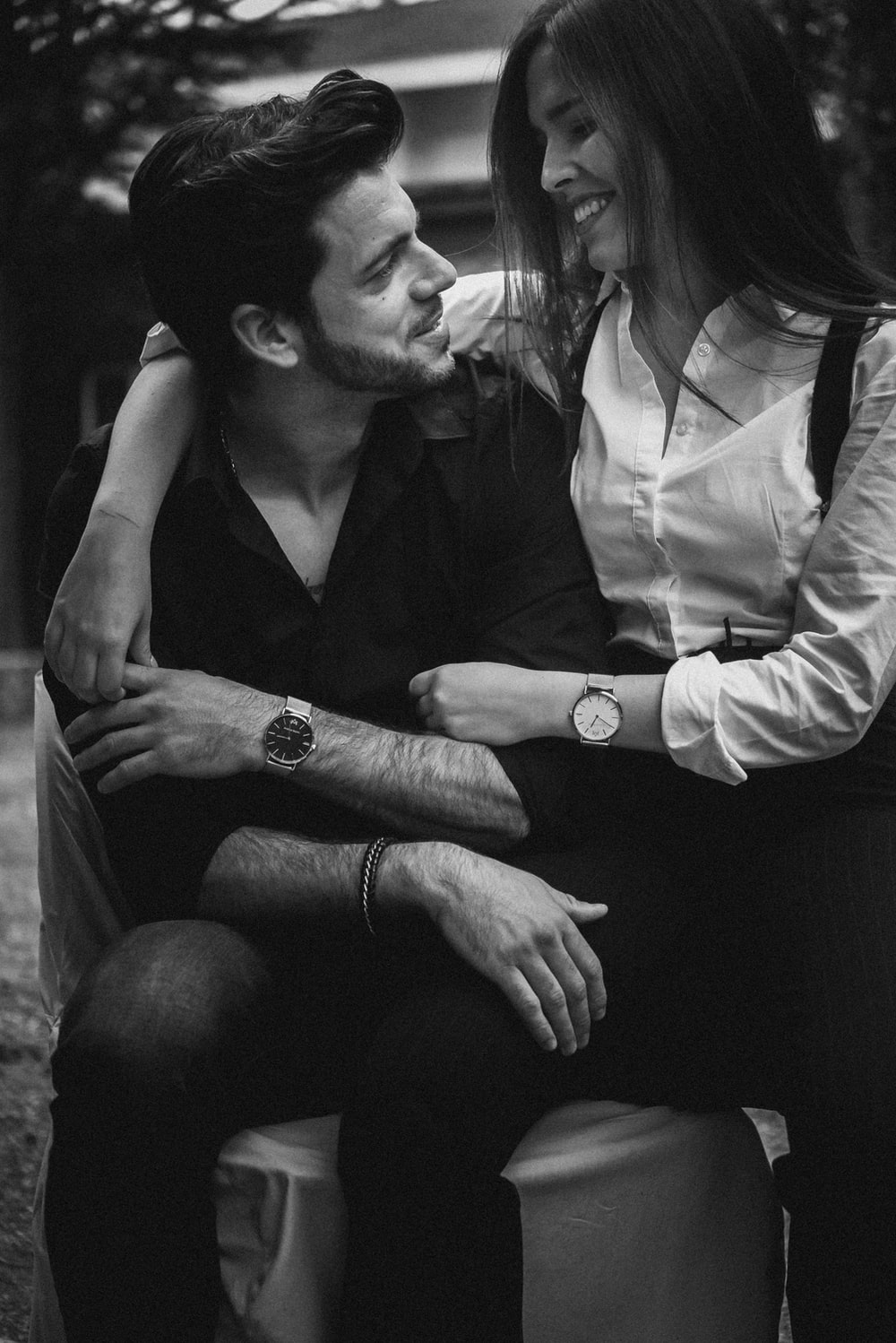 grayscale photography of couple sitting on chair while looking each other