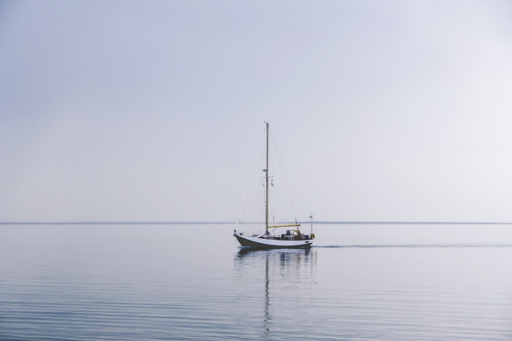 white boat in middle of ocean during daytime