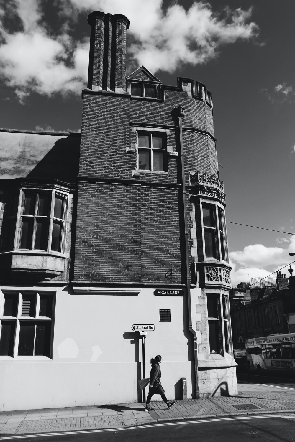 grayscale photography of person walking on street beside building