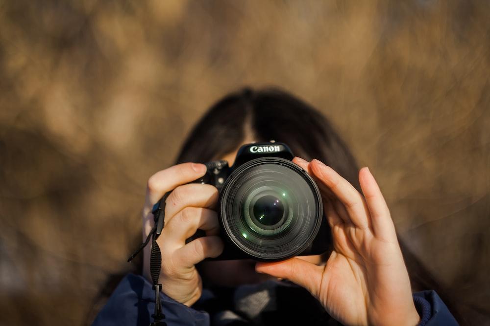 woman holding Canon camera