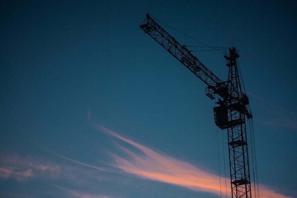 silhouette photo of tower crane