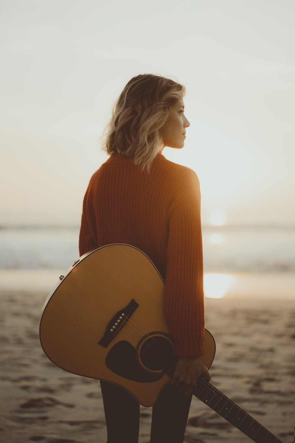woman standing while holding acoustic guitar