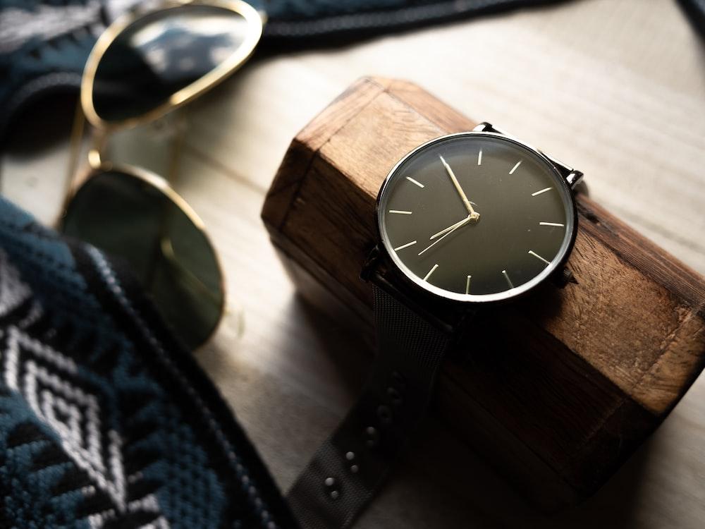 analog clock on case beside sunglasses