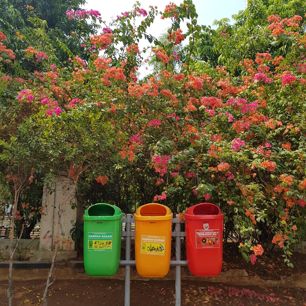 three assorted-color garbage cans