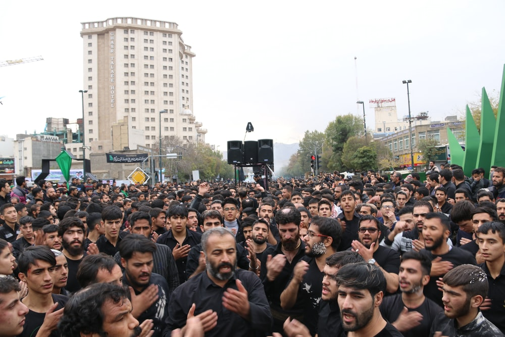 crowd of people gathered near high-rise building