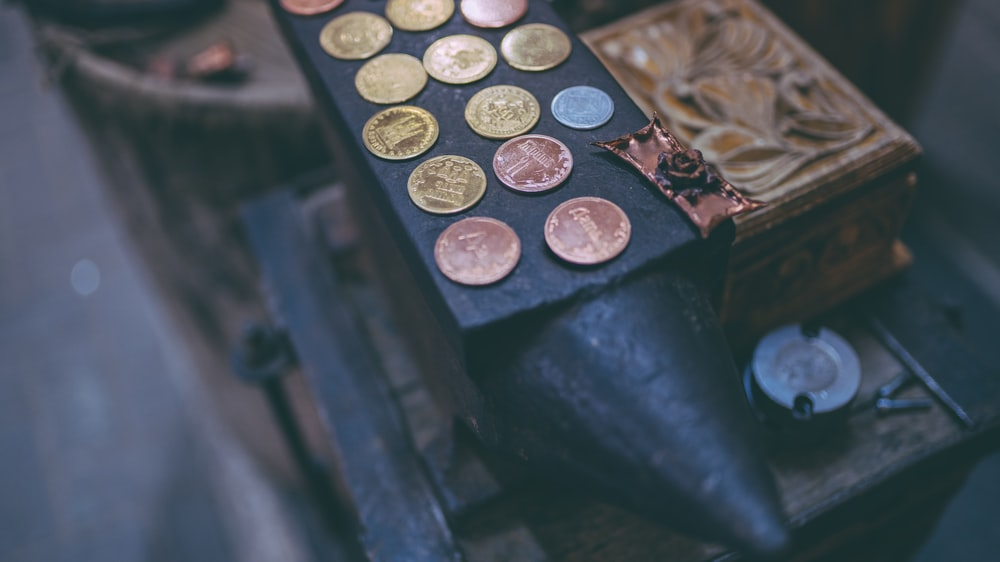 coins on black anvil