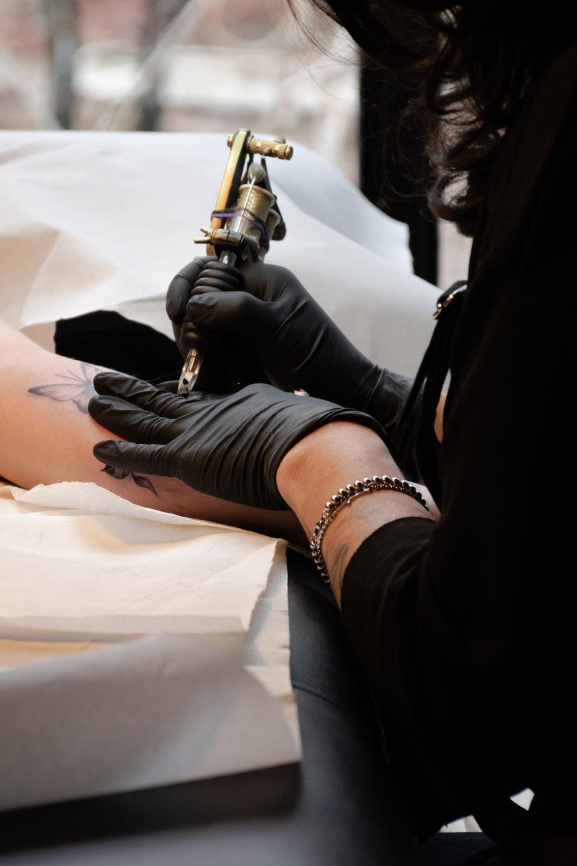 woman holding brown tattoo machine