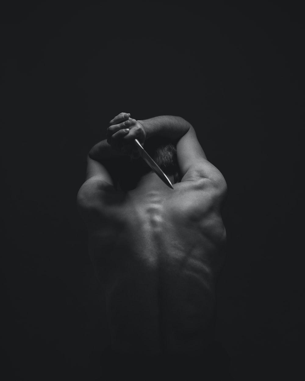 man holding gray dagger