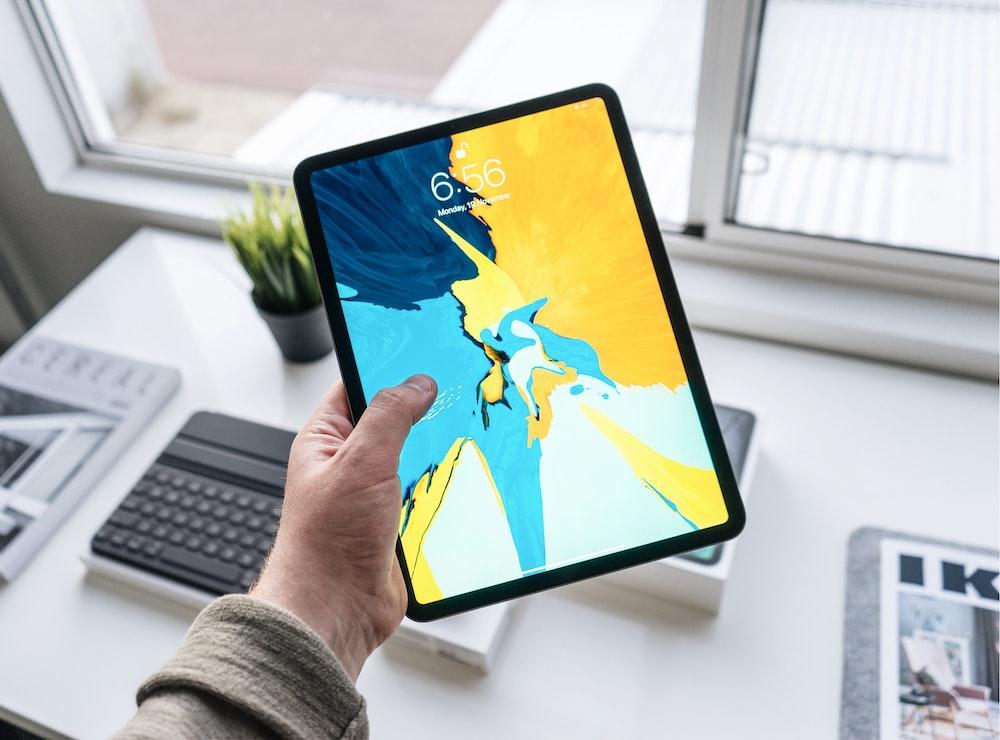 person holding turned-on black iPad