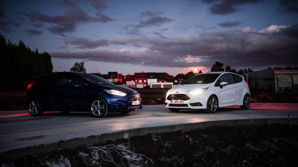 two blue and white Ford Fiesta RS 5-door hatchback on road