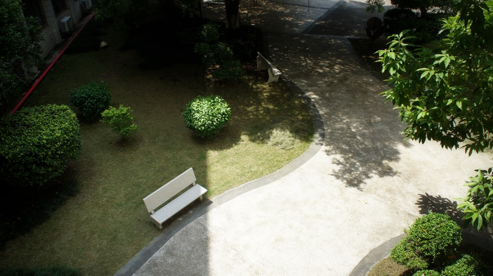 used white bench next to concrete pathway