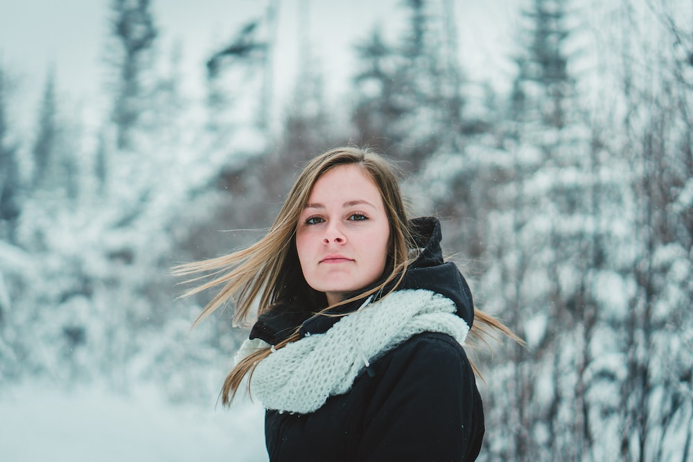 selective focus photography of woman wearing black coat on snow field
