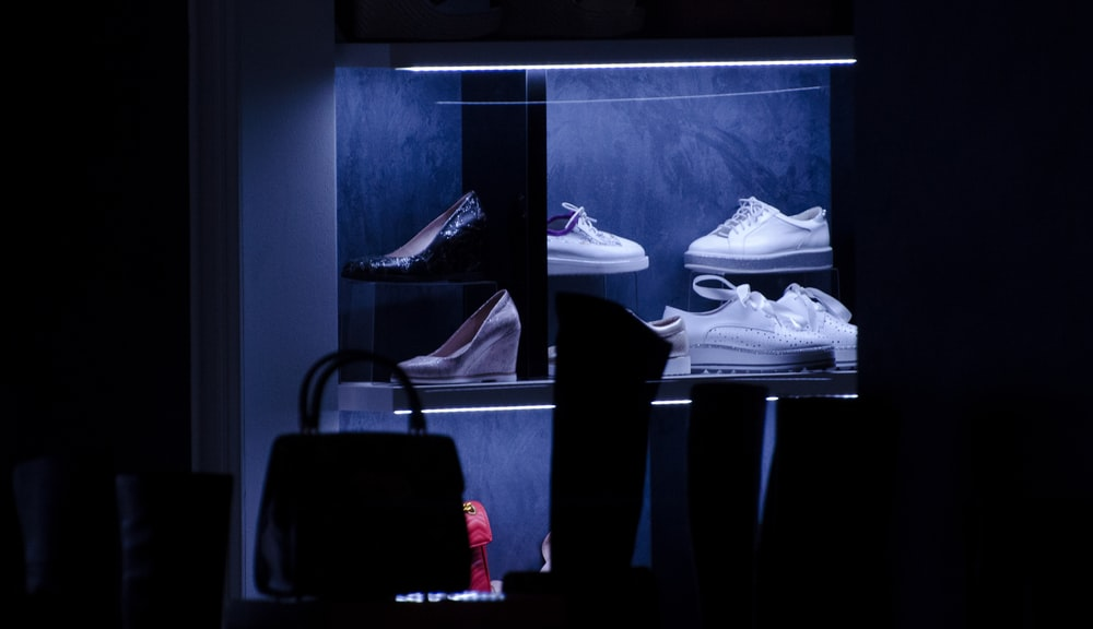 lit shoe display collection inside a dark room