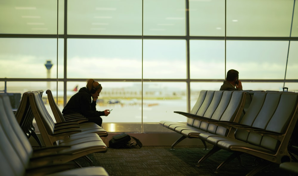 man and woman sitting on gang chair in airport