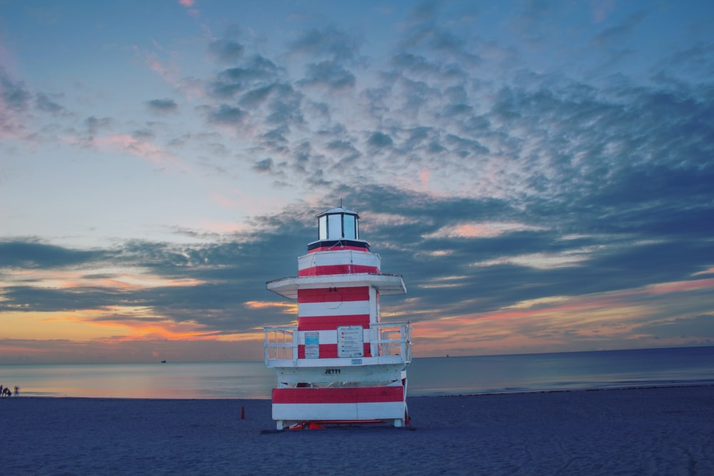 white and red lifeguard watchtower during cloudy daytime
