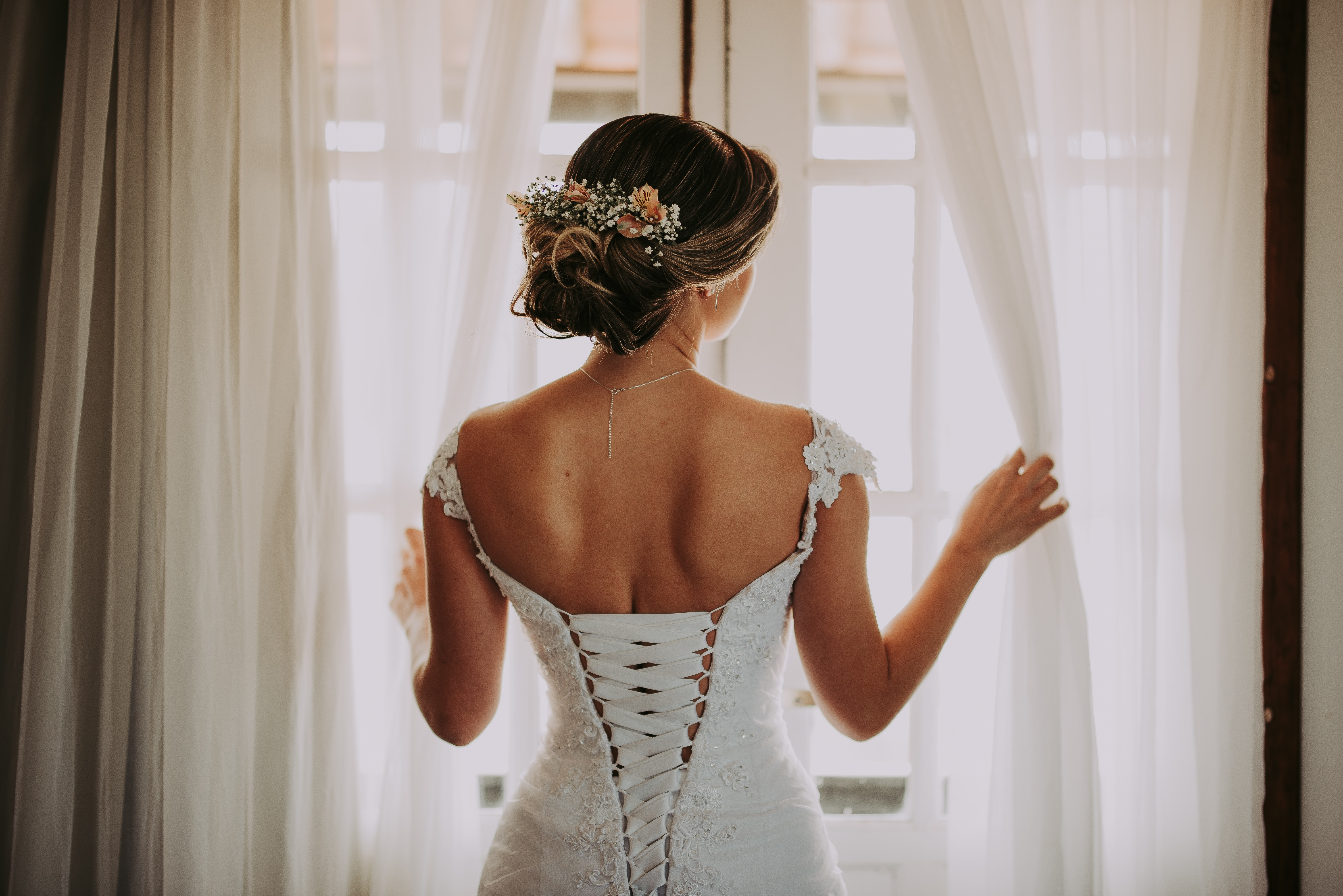 woman in wedding dress standing near window looking outside while holding the curtains