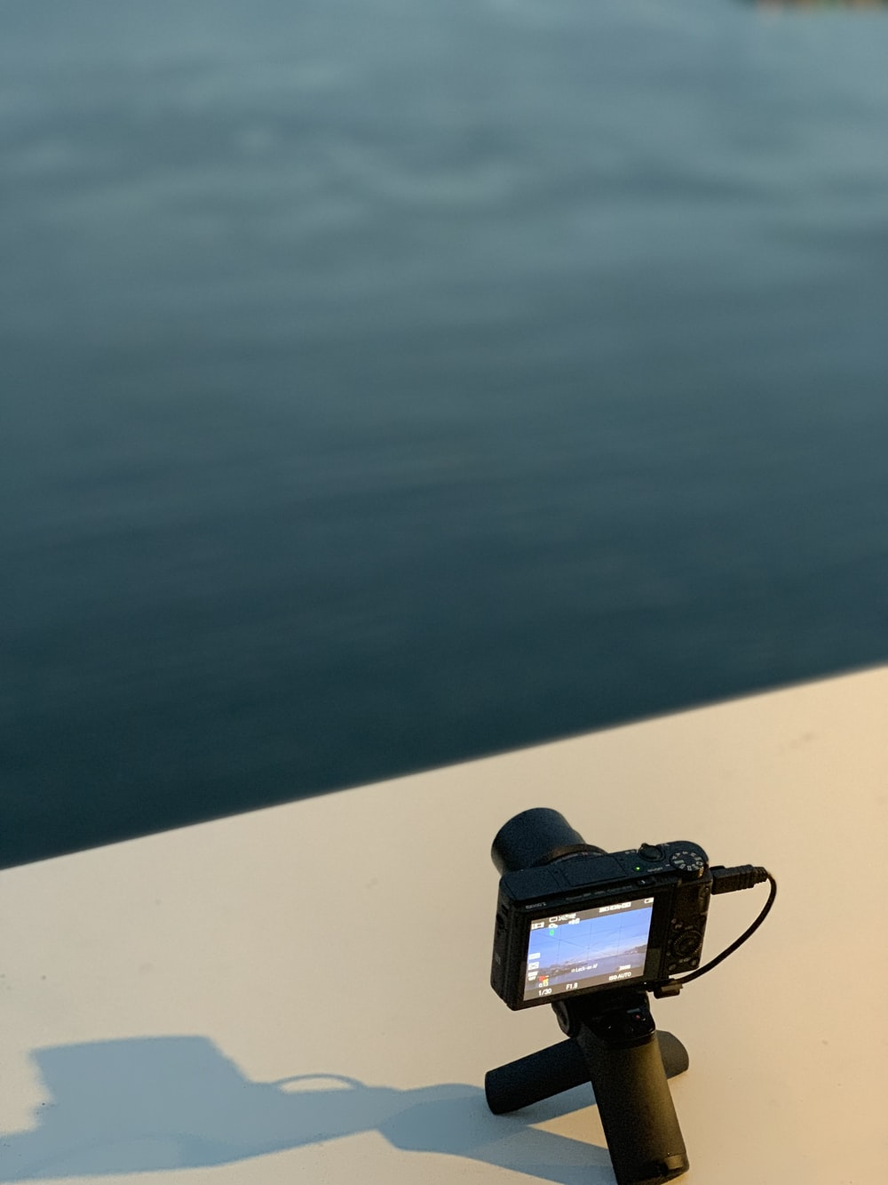 black action camera on white surface