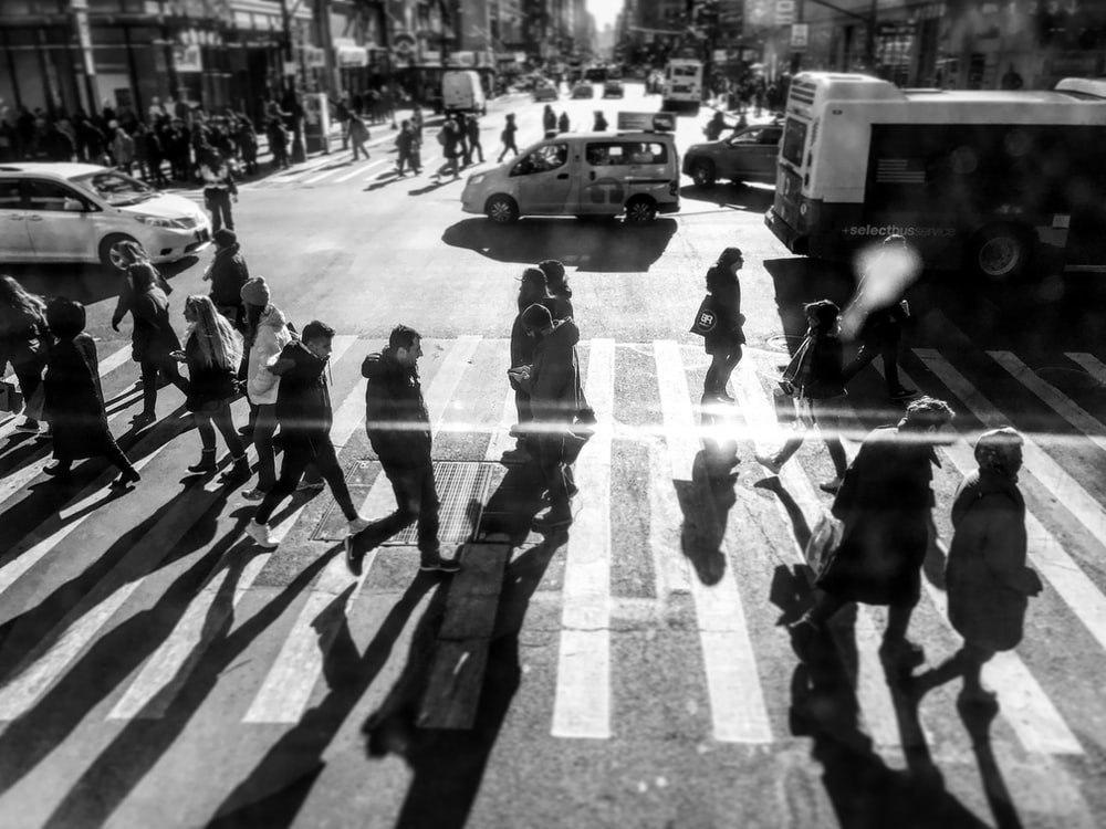 grayscale photo of people passing by on pedestrian lane during daytime