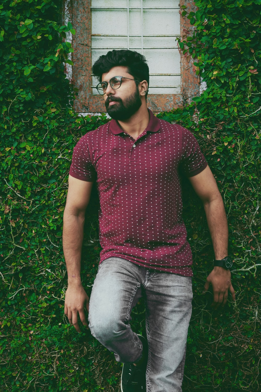 man in maroon polo shirt leaning on wall and green plants