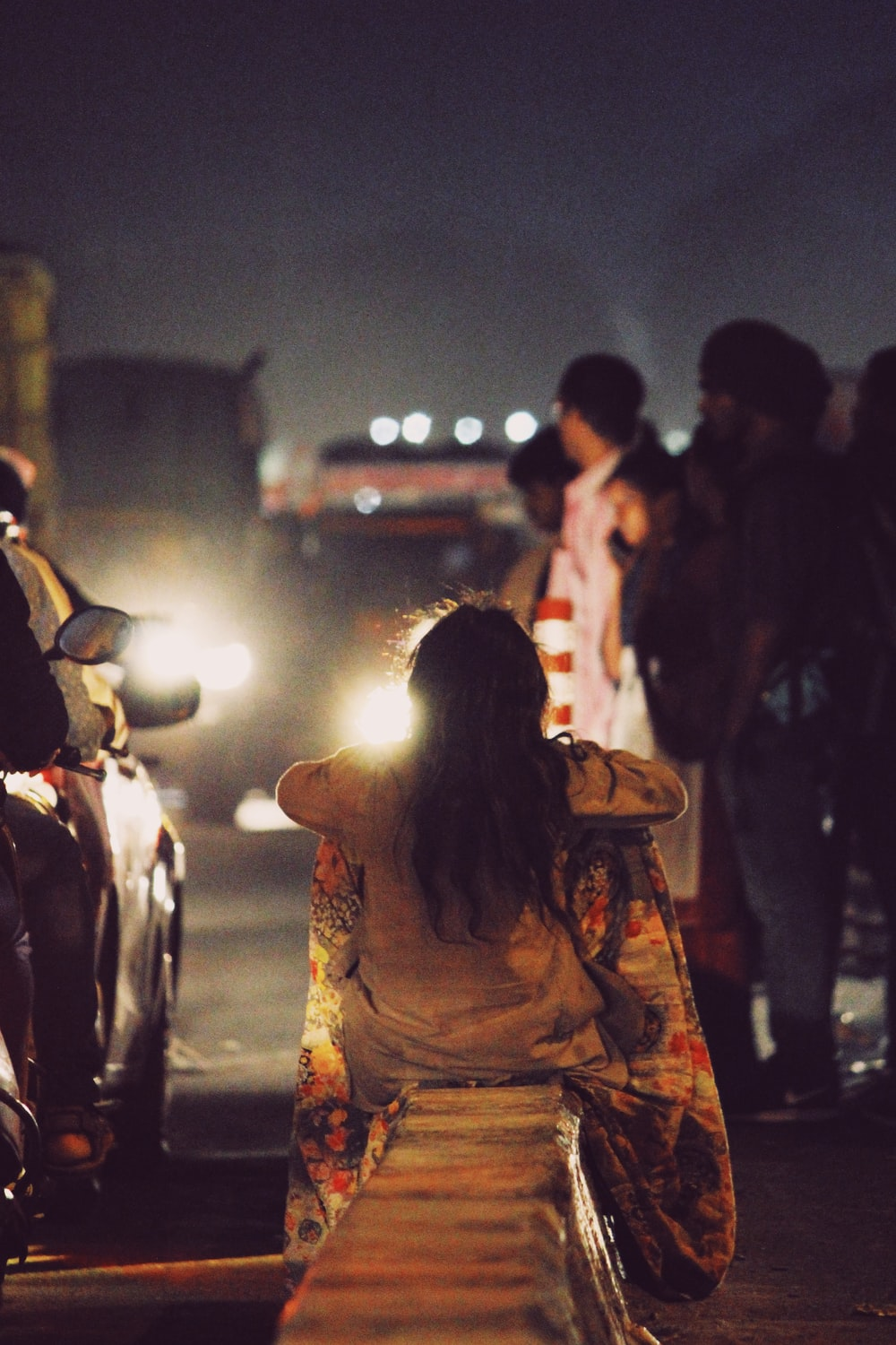 woman sitting on concrete barrier on street