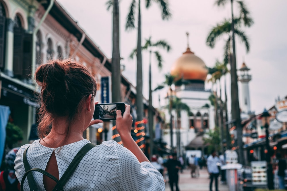 selective focus photography of woman taking photo