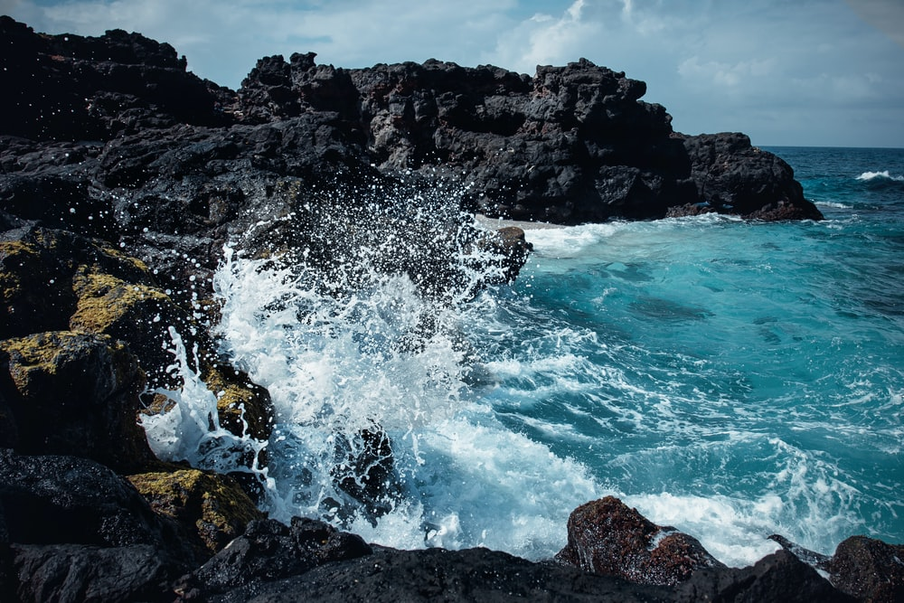 sea waves splash on rock formation at daytime