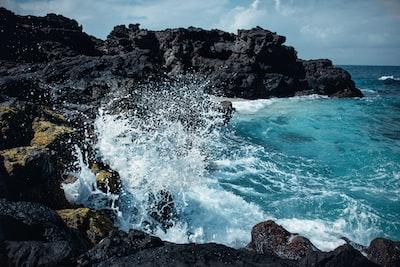 sea waves splash on rock formation at daytime sea zoom background