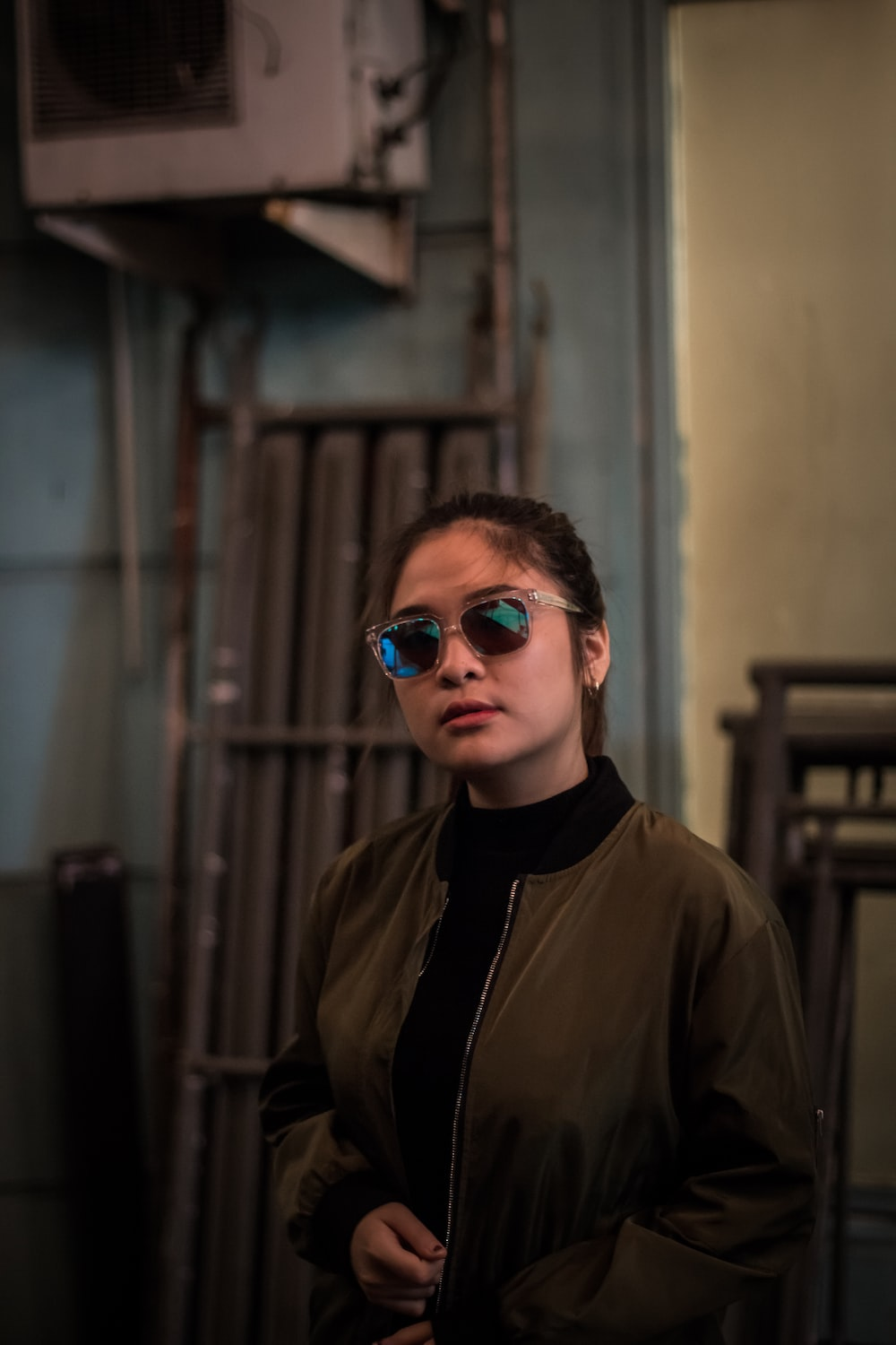 woman wearing sunglasses and brown jacket