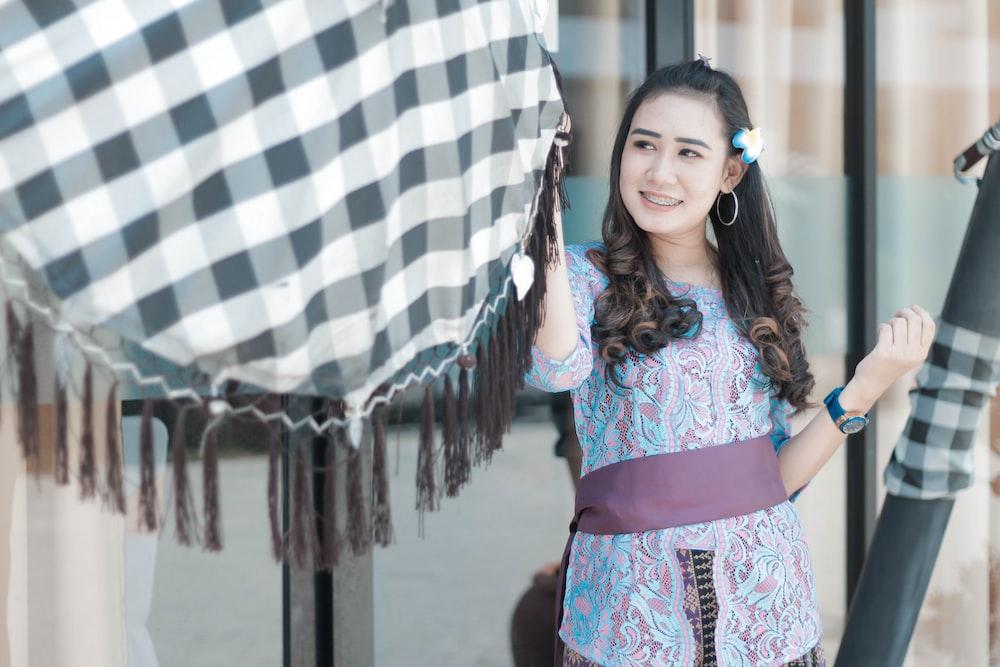 smiling woman holding hanging textile at daytime