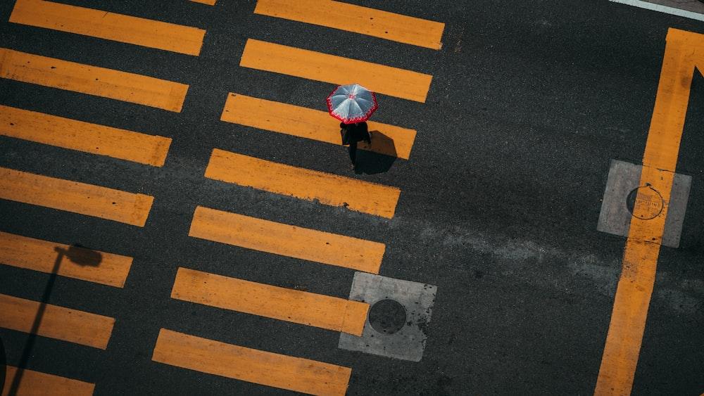 bird's-eye photography of person walking on pedestrian lane