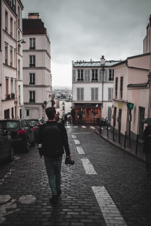 man walking on road near houses