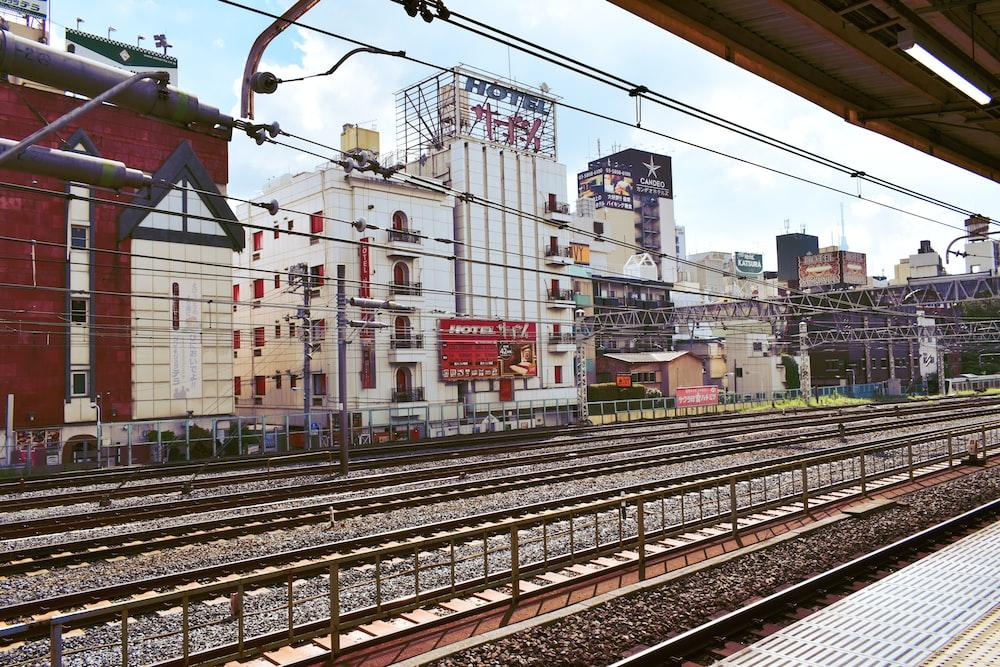 train rail near city buildings during daytime