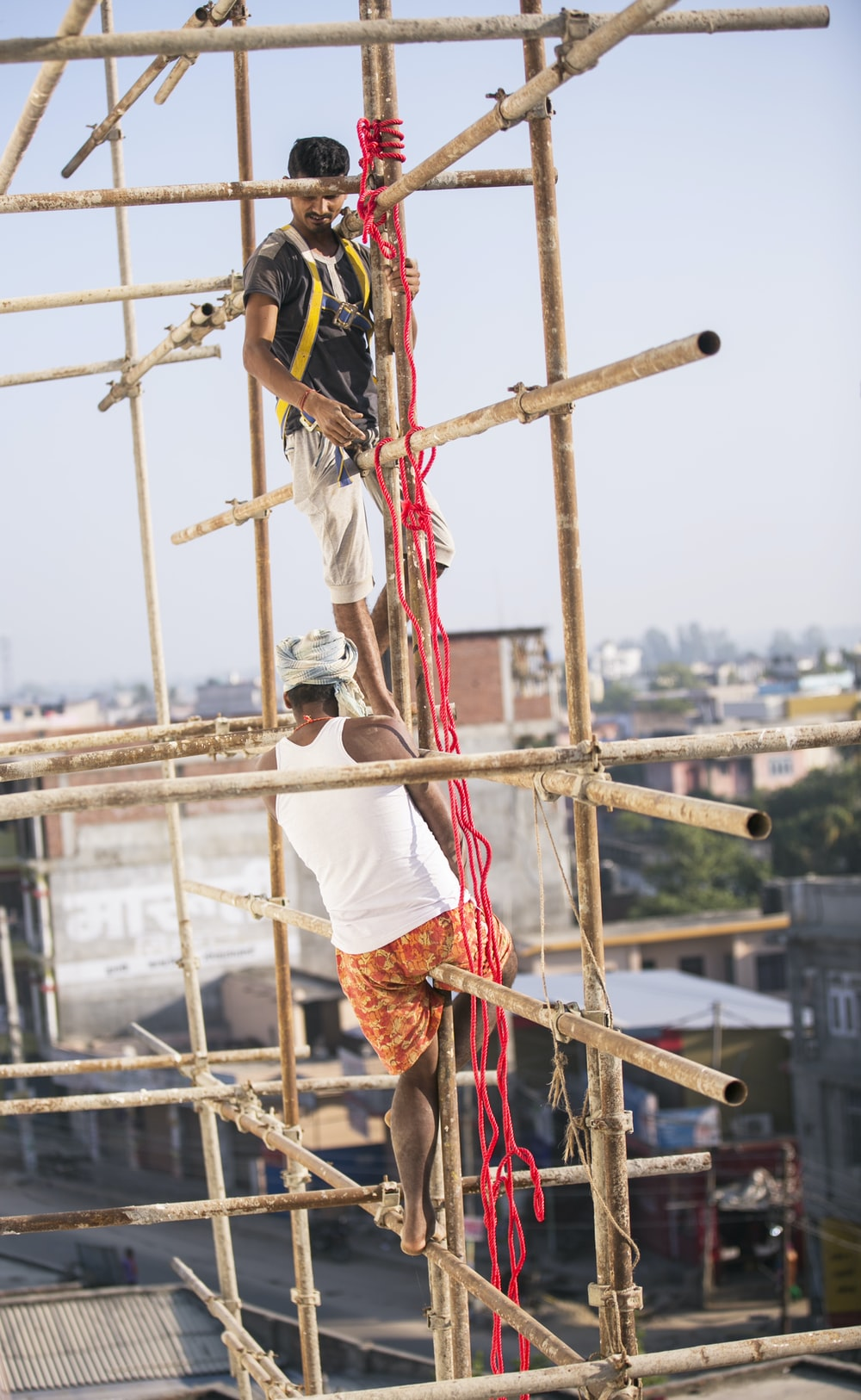 two men climbing on brown bamboo scaffolding at daytime