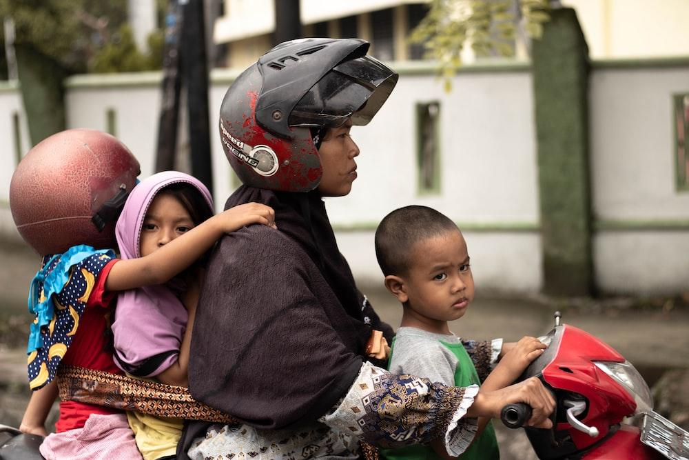 man riding motorcycle with 3 kids at daytime
