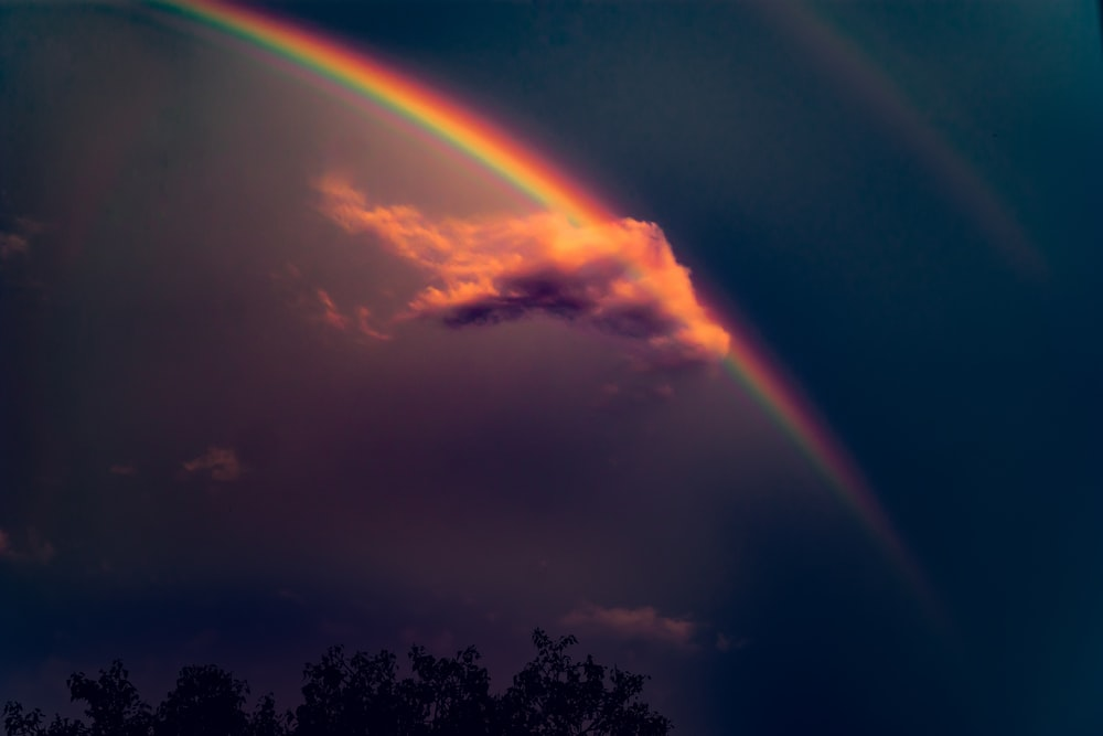 rainbow on blue sky with gray clouds during daytime