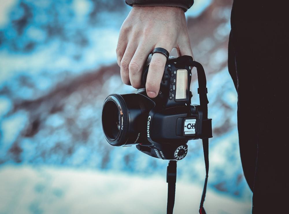 person black Canon DSLR camera