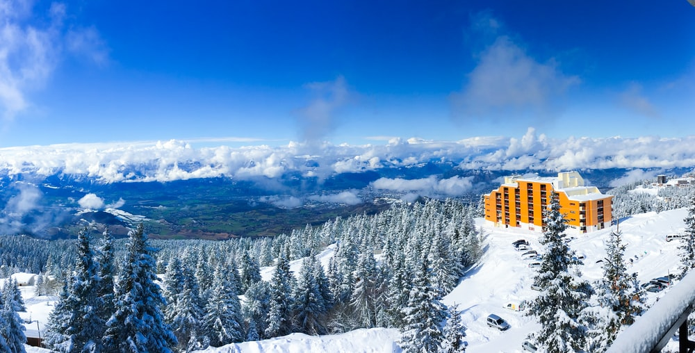 yellow building on snow covered mountain during daytime