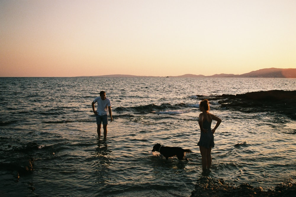 man and woman standing on sea during golden hour