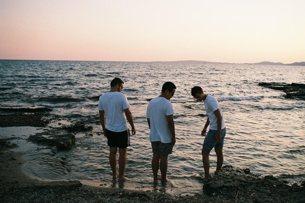 three men wearing white shirts standing on seashore