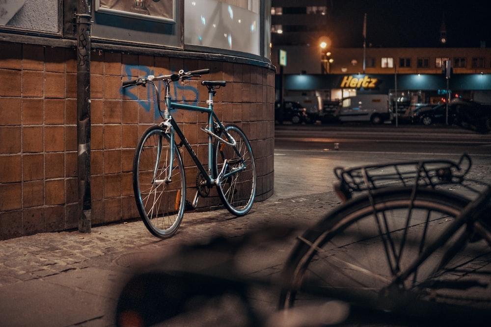 blue and black bike parking near wall