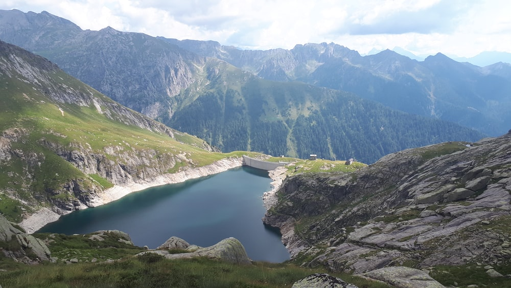 high-angle photography of lake surrounded by mountain range