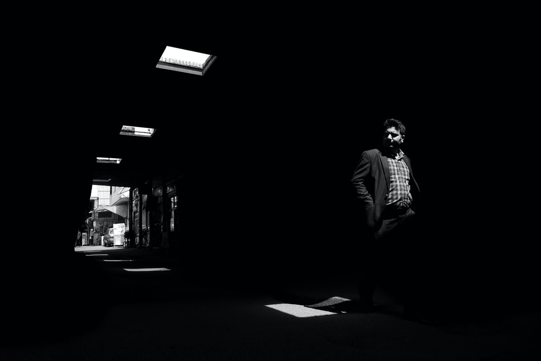 grayscale photography of man walkning in room