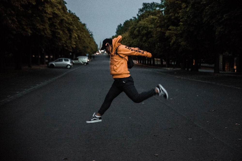 person in orange hoodie jumping on middle of road