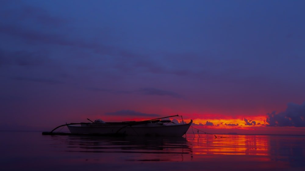 white boat under cloudy sky during sunset