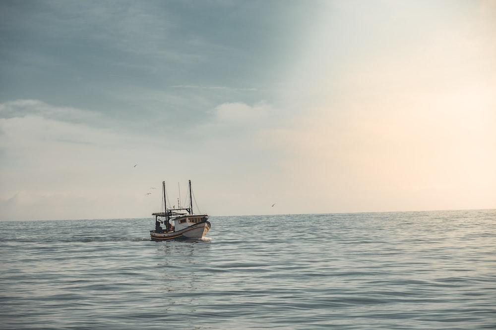 white boat sailing on ocean