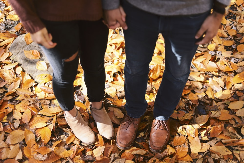two person standing on dried leaves at daytime