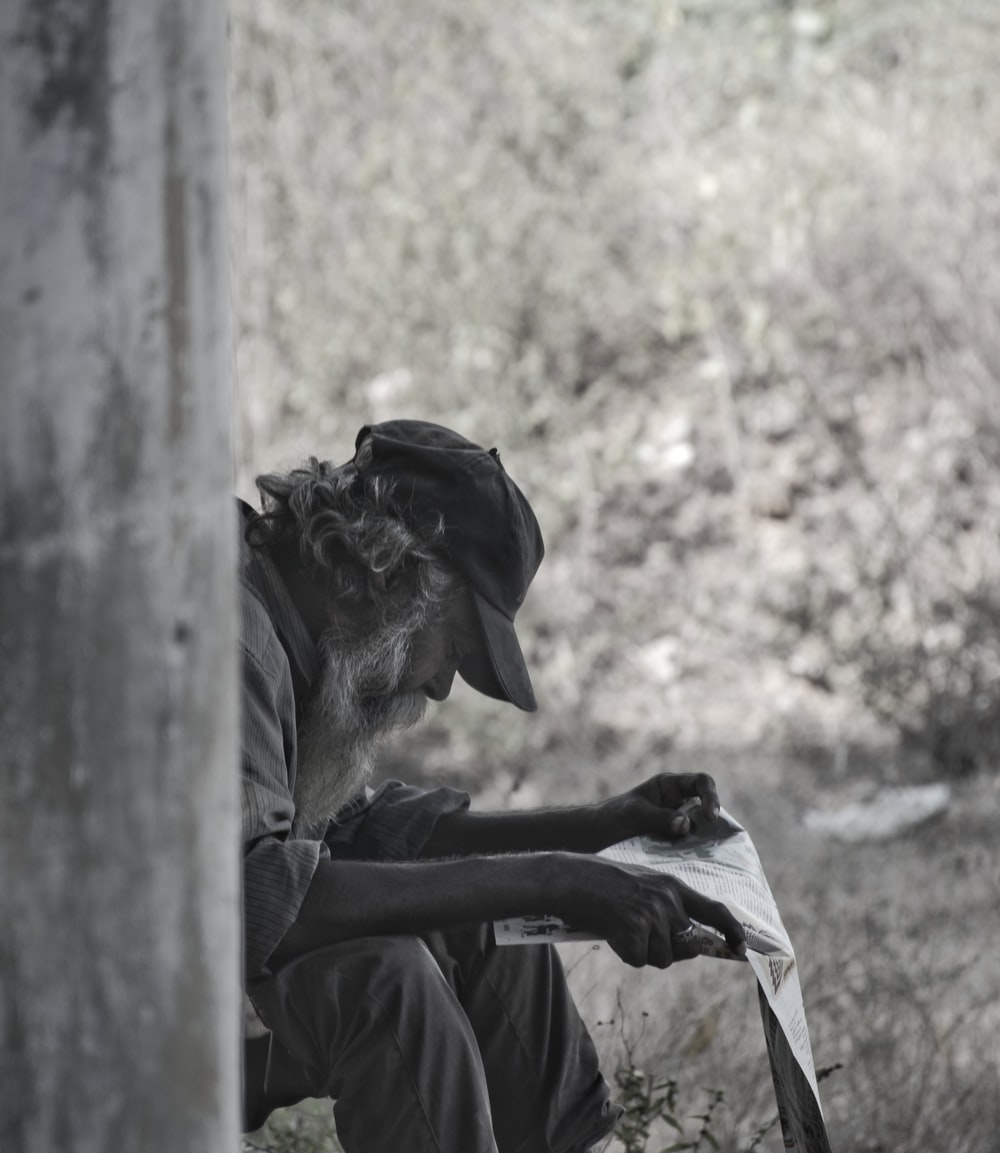 man reading grayscale photography