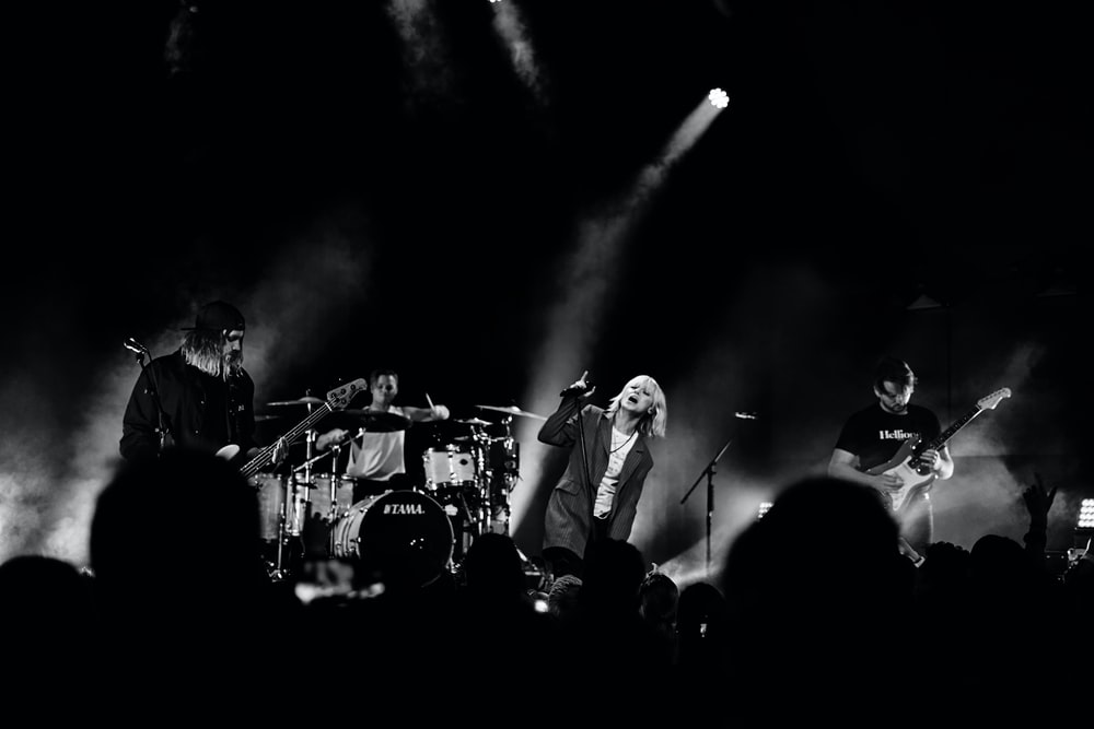 grayscale photography of band performing on stage