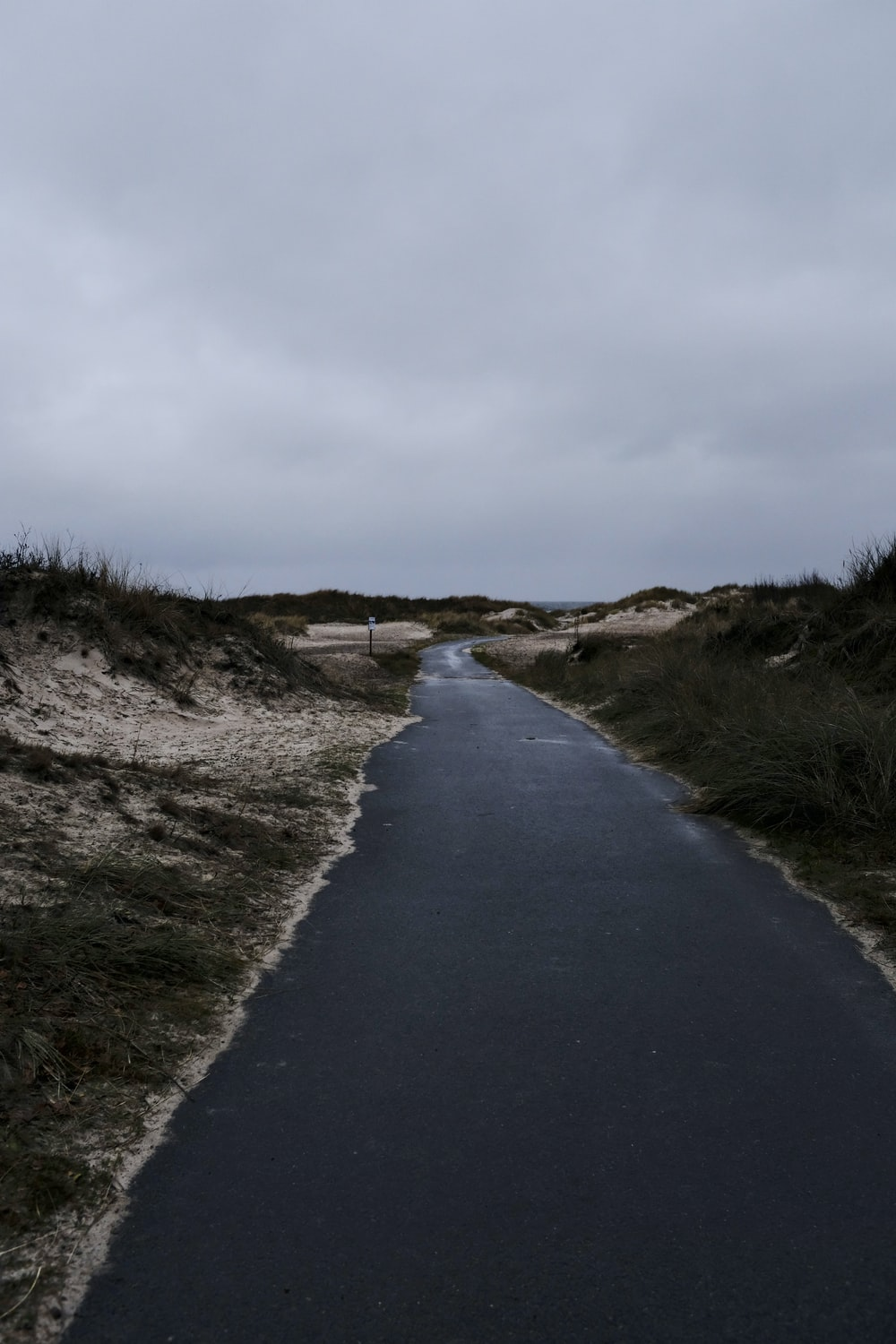 empty paved road under white sky